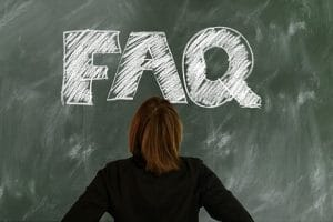 woman looking at the word faq on chalkboard