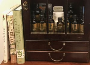 "display of books and herbal products in a small antique apothecary chest linked to the article ""What should I stock in my Medicine Cabinet?"""